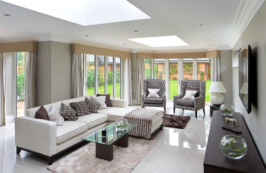This living room features light gray walls and sparkling tiles flooring along with skylights.