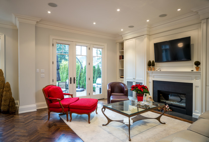A living room featuring fancy seats and a glass top center table set on a rug covering the stylish hardwood flooring. The area offers a fireplace along with a large widescreen TV on top.