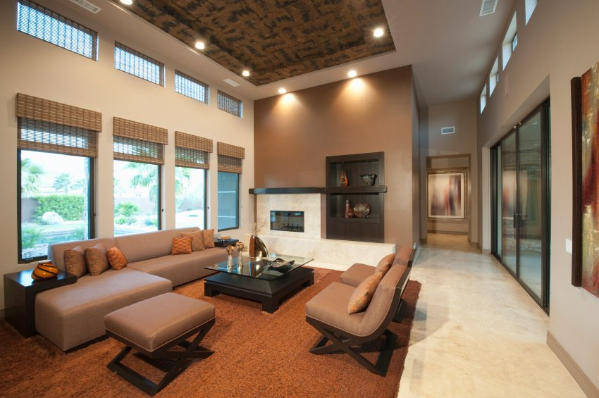 A modish large living room featuring an elegant brown set of seats matching the brown rug covering the classy tiles flooring. The high ceiling adds style to the room.