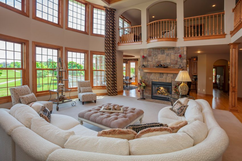 Large living room with a nice and comfortable white sofa set along with a stone fireplace. The area is under the tall ceiling.