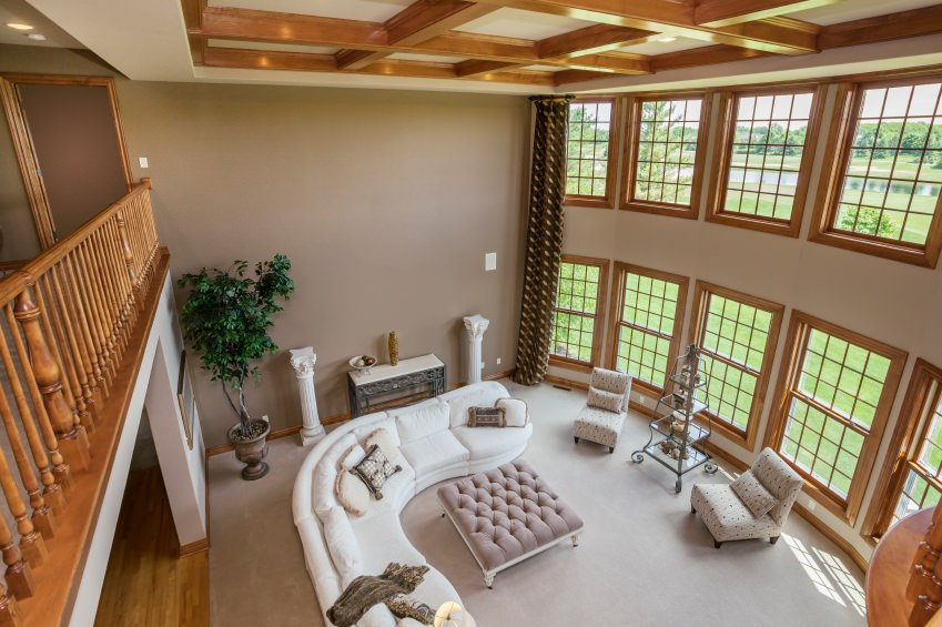A shot of this living room from the home's second floor. The living room boasts a massive rug covering the hardwood flooring. The high coffered ceiling adds elegance to the home.