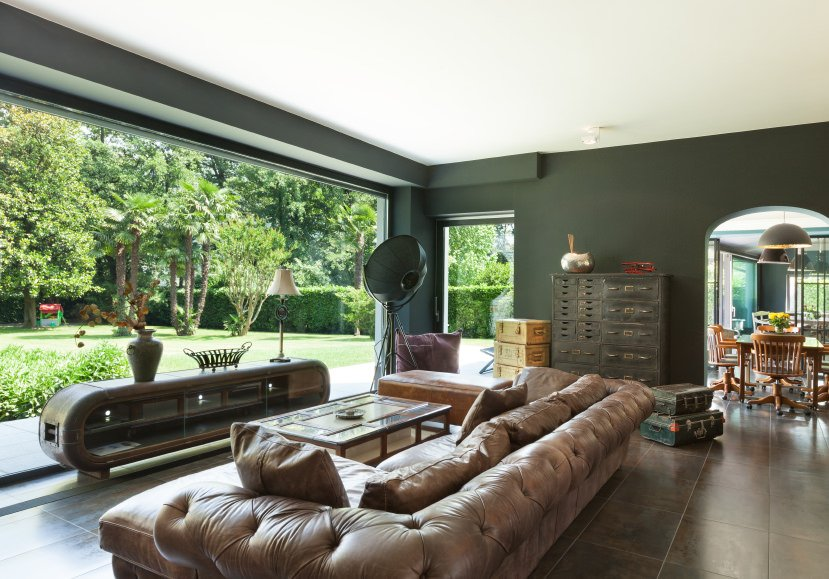 Modish living room with an elegant leather sofa and dark green finished walls. The tiles flooring looks stunning as well.