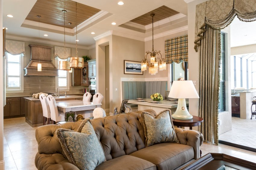 Small great room featuring classy tray ceiling lighted by gorgeous pendant lights and chandelier.