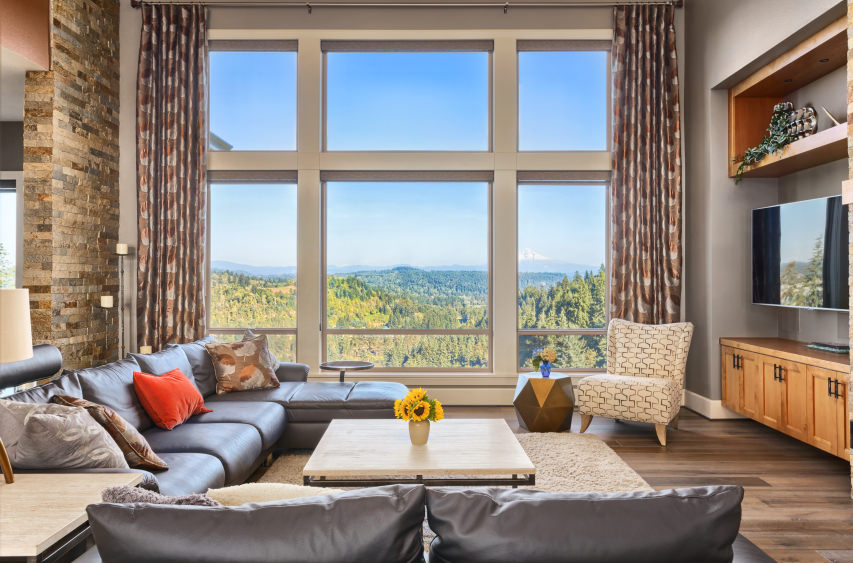 This living room offers a gray sofa set along with a widescreen TV in front. There are glass windows overlooking the marvelous surroundings.