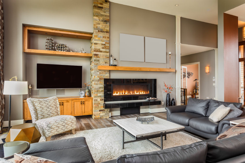 A living room featuring a gray sofa set along with a large widescreen TV and a fireplace.