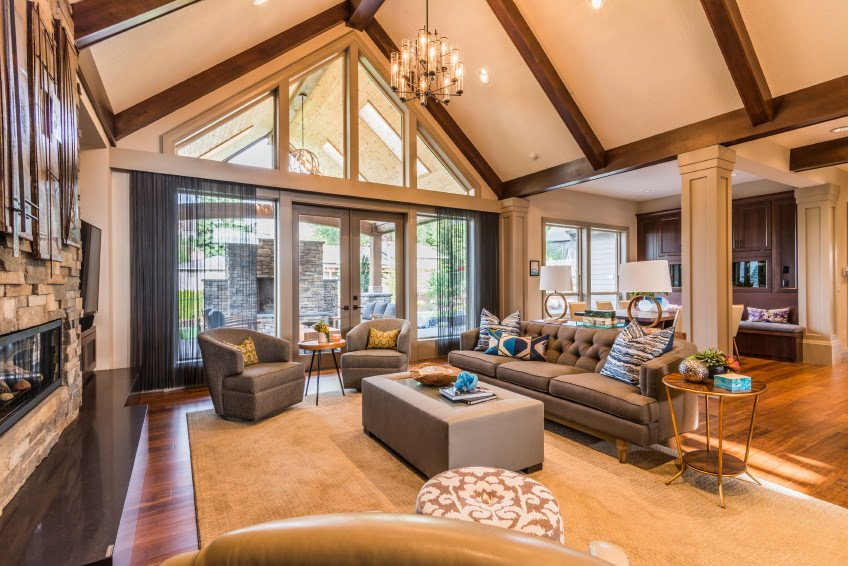 A modish formal living room with a tall vaulted ceiling with exposed beams lighted by a glamorous chandelier. The room has a cozy set of seats and a fireplace.