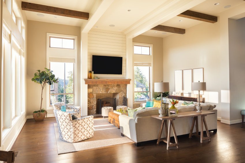This living room offers classy seats and a fireplace, along with a widescreen TV on top of it. The room also features hardwood flooring and a tall ceiling with beams.