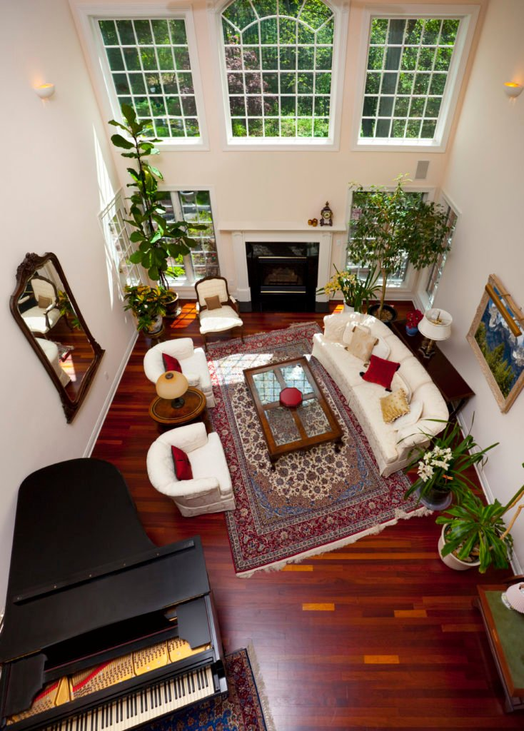High ceiling living room showcases white round back sofa set and a glass top coffee table that sits on a vintage rug over the rich hardwood flooring. It includes a grand piano with matching rug.