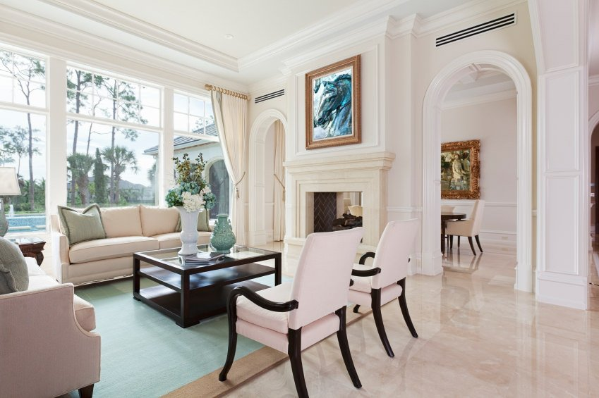 White living room with cozy seats, a fireplace and a sparkling tiles flooring.
