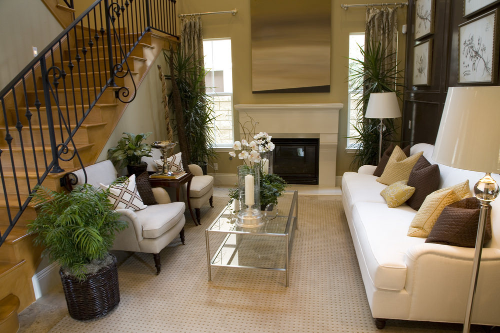 Tropical living room features a white sofa facing the armchairs in front of a wooden staircase framed with ornate wrought iron railing.