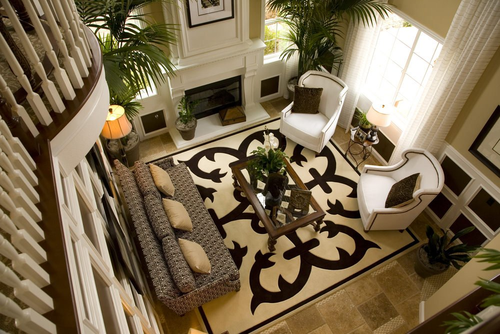 A top view of this living room designed with black and white coffered walls that complement the area rug. It has printed sofa and white wingback chairs with a glass top coffee table in the middle.