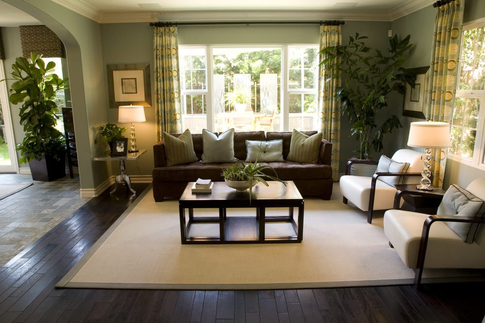 Fancy table lamps illuminate this spacious living room along with natural light that flows through the paneled glass windows. It has dark wood plank flooring and sage green walls mounted with wall arts.