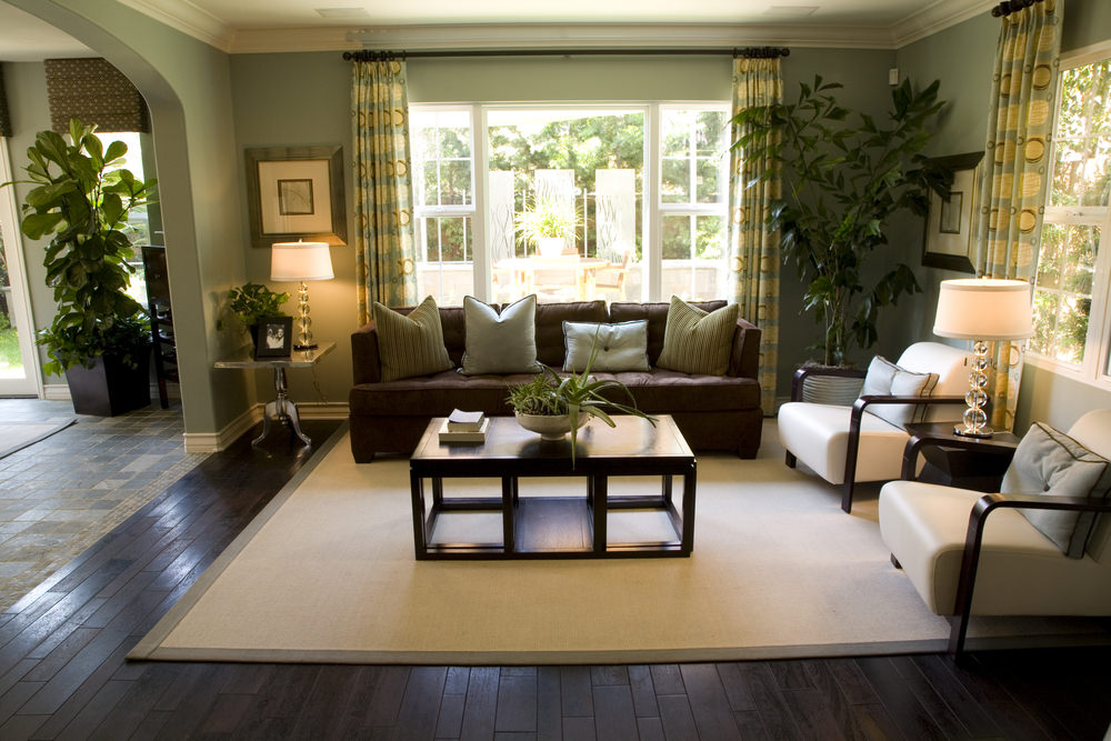 A medium-sized living room boasting a dark hardwood flooring topped by a classy rug matching the white seats on the side.
