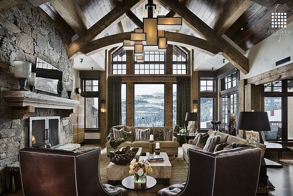A large rustic formal living room featuring a set of gorgeous seats along with a large fireplace under the tall rustic vaulted ceiling.