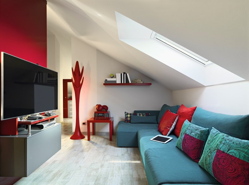 Small living room featuring a widescreen TV set on the handsome red wall. The room also offers a cozy blue sofa set under the shed ceiling with a skylight.