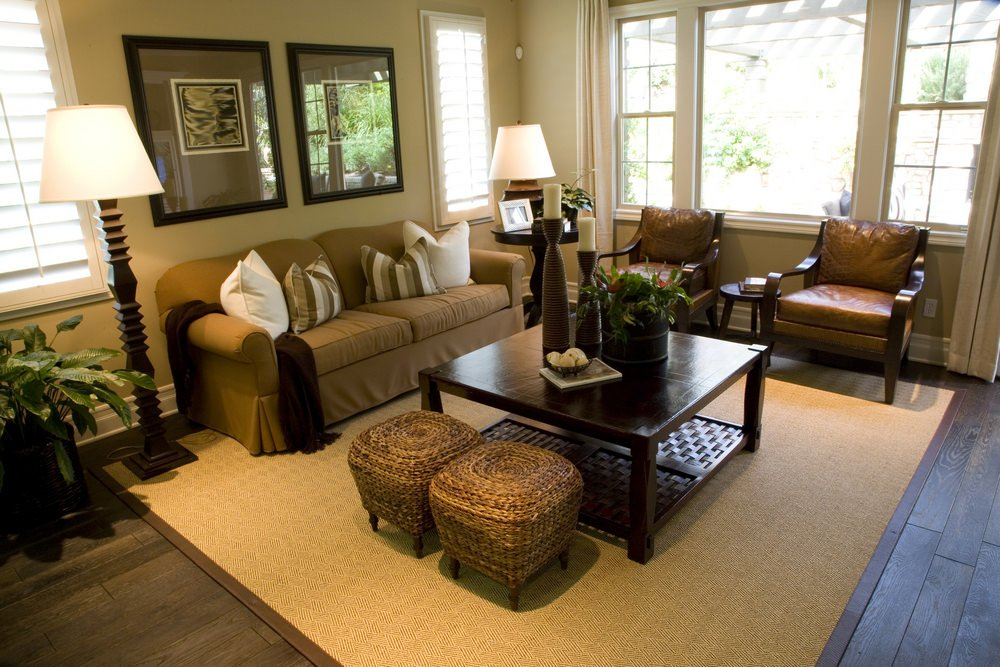 Simple yet classy living room with brown seats and a simple rug on top of the hardwood flooring.