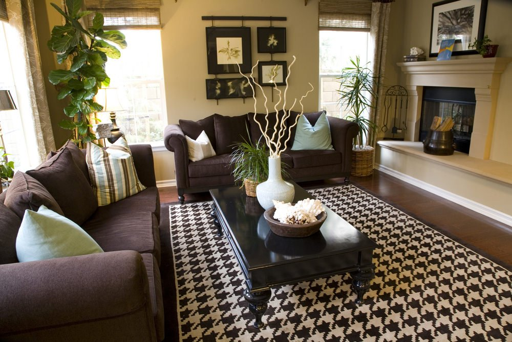 Tropical living room accented with a striking area rug that lays on hardwood flooring. It has a fireplace sitting on a beige platform clad with a baseboard molding.