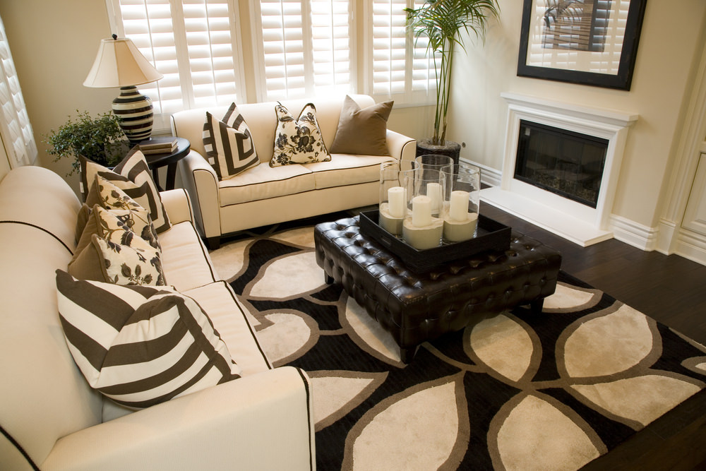 White living room boasts a pair of sofas with black linings and various styled pillows. It includes a black tufted ottoman that sits on a black patterned rug.