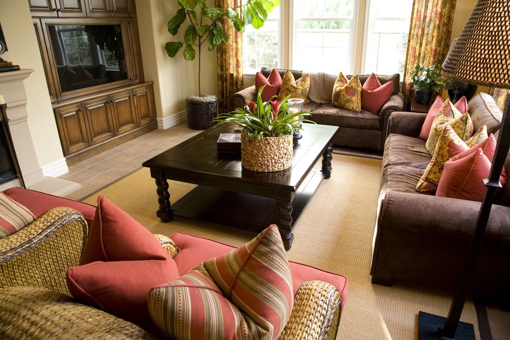 This living room offers comfortable seats and a classy rug covering the tiles flooring. The room also features multiple indoor plants.