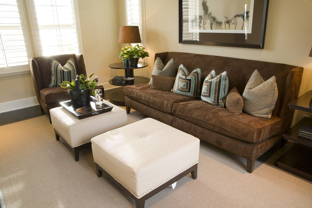 This living room offers brown comfy seats and white ottomans set on the room's rug covering the hardwood flooring.
