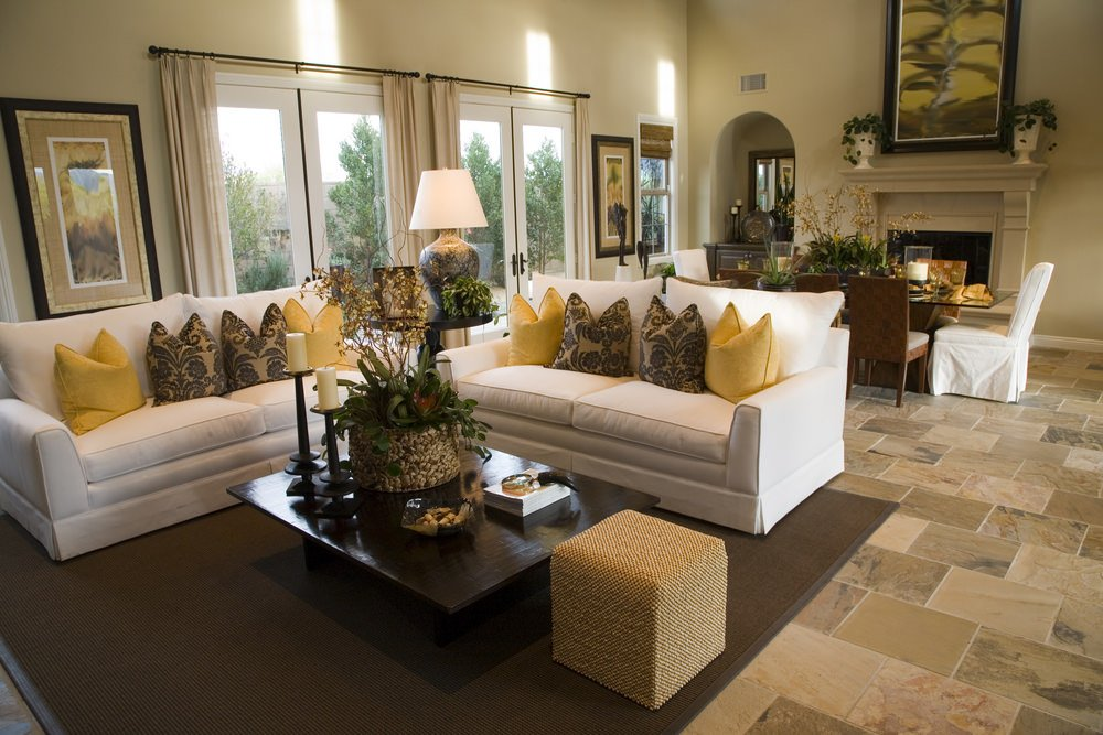 This living room offers lovely couches and throw pillows. The brown rug looks good with the tiles flooring.