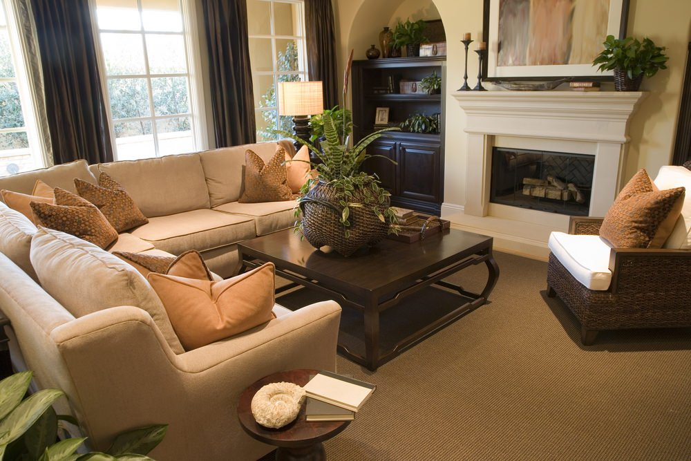 Small living room with a comfy beige sofa set and a brown carpet flooring along with a small fireplace.