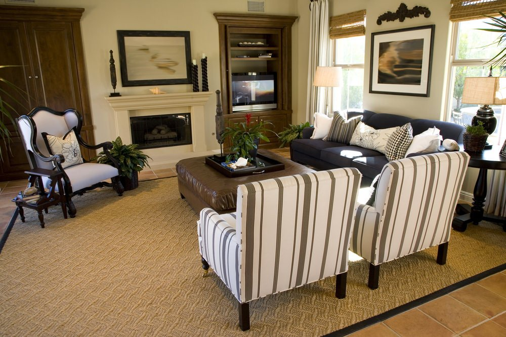 Formal living room showcases white striped armchair and wooden accent chair contrasted with a dark gray sectional. It has a terracotta tiled flooring topped with a textured area rug.