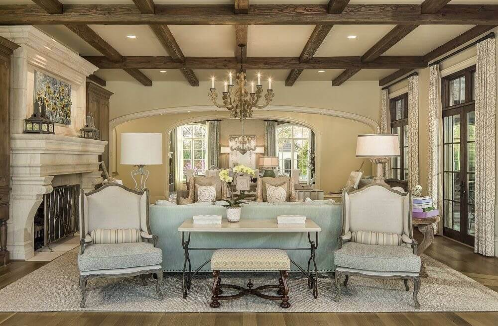Large formal living room lighted by a glamorous chandelier hanging from the ceiling with rustic beams. The room also has a large fireplace.
