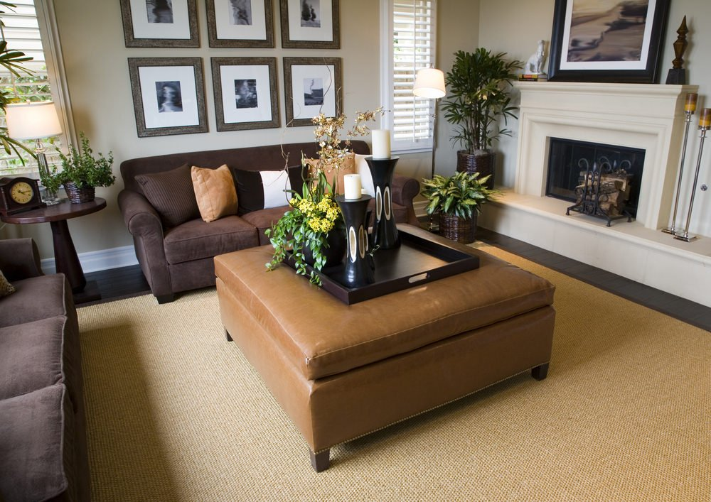A small formal living room boasting brown cozy seats and a fireplace. Multiple attractive wall decors hang from the beige wall.