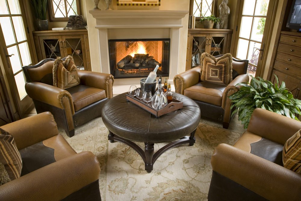 Cozy living room offers leather armchairs surrounding a tufted coffee table over a shabby chic rug and facing the white fireplace.