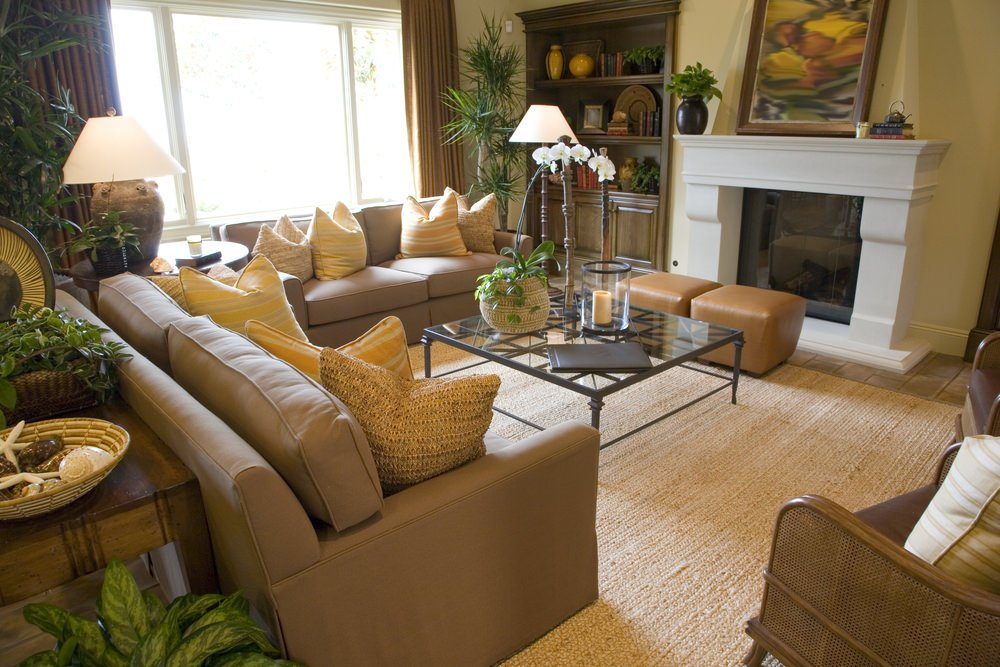 This formal living room boasts a set of classy seats and an attractive center table, along with the fireplace.