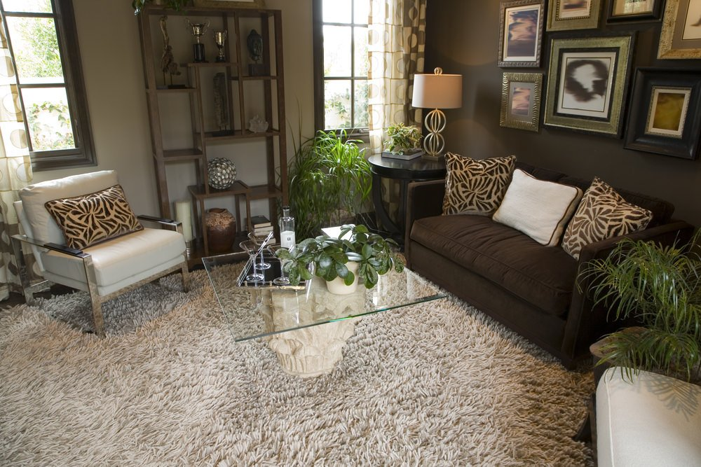 Small yet classy living room featuring a comfy set of seats and a charming glass top center table. Multiple artistic wall decors hang from the brown wall.
