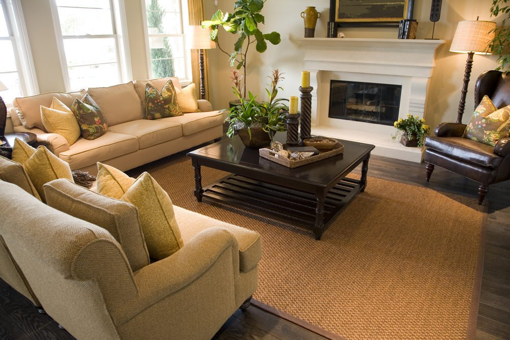 A modish formal living room offering a cozy beige sofa set and a fireplace along with potted indoor plants.