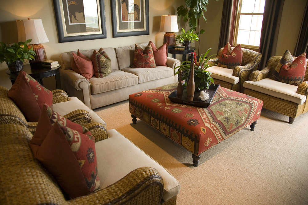 The throw pillows of this living room match the cloth of the center table. The seats and the tables are set on the lovely carpet flooring.