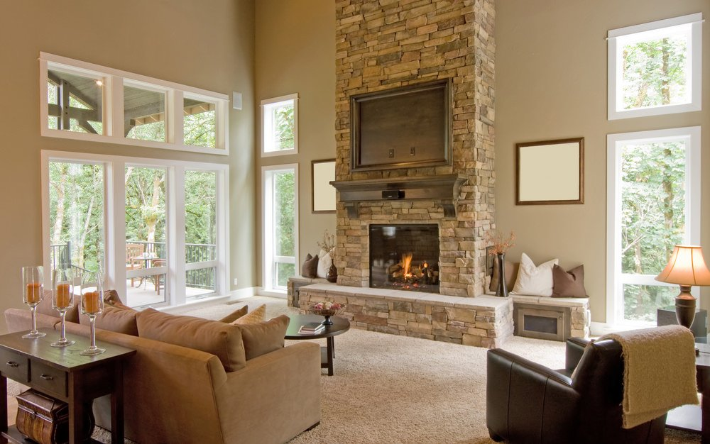 Another look at this spacious living room featuring a cozy sofa set in front of the large stone fireplace with a built-in TV on the stone wall.