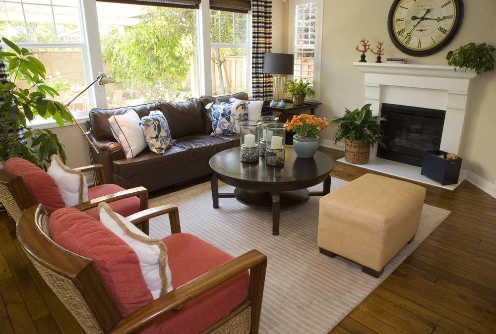 A small living room set on the home's hardwood flooring. The space also features a small fireplace on the side.