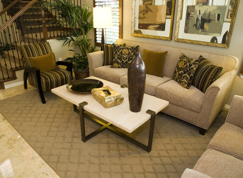 A living room offering a classy sofa set with a rug set on the charming tiles flooring.