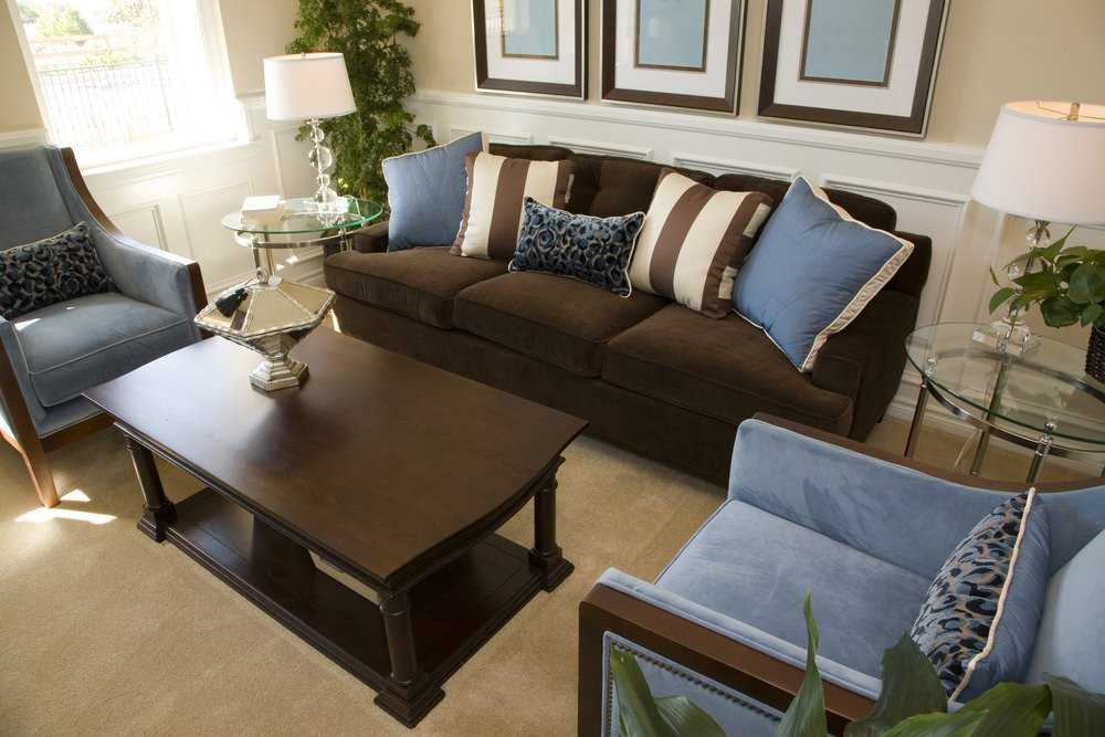 This room offers a stylish and cozy set of seats set on the home's lovely carpet flooring. The indoor plants add color to the room.