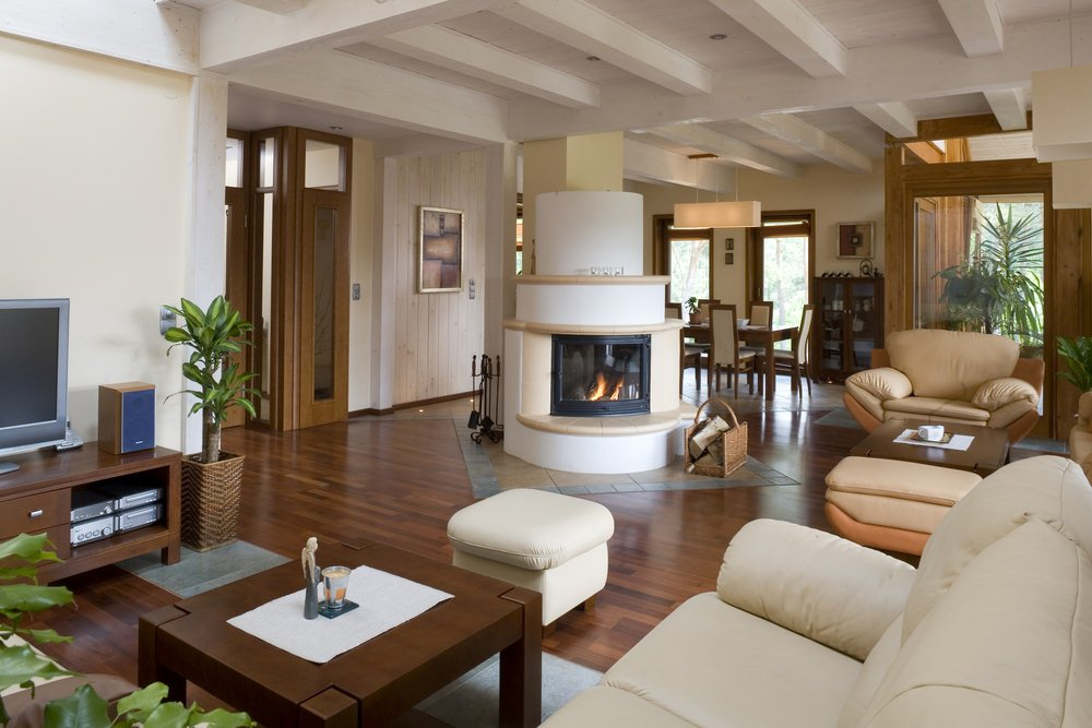 Large formal living room with hardwood floors and a fireplace set on the center of the room.