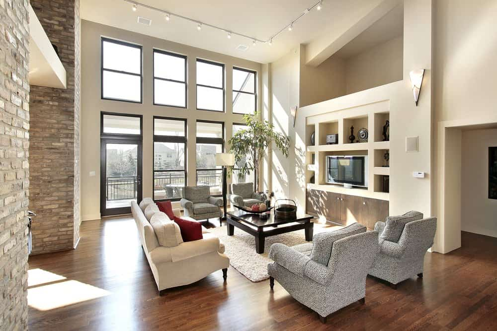 Contemporary living room with 2-story ceiling, track lighting, large windows, and hardwood flooring.