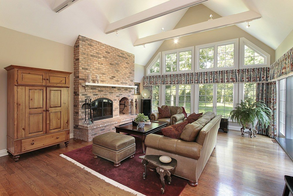 Spacious formal living room with a classy fireplace and a charming red rug. The area features tall glass windows and high vaulted ceiling with beams.