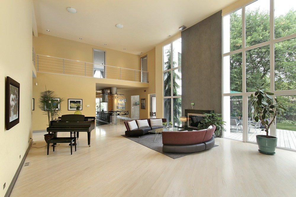 Large living space featuring a black piano and a pair of modish seats along with a glass top center table near the modern fireplace.