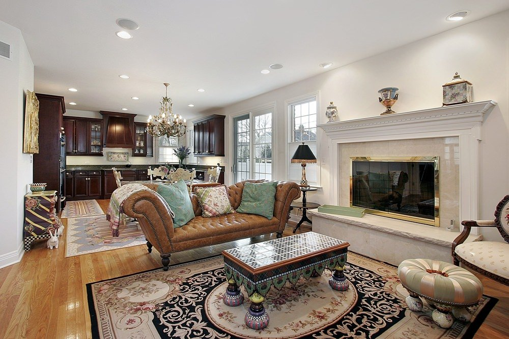 This great room offers a living room with a fireplace, along with a dining table set with a gorgeous chandelier.
