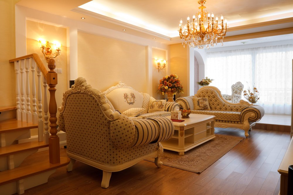 A living room featuring a set of classy seats and is lighted by glamorous chandelier set on the tray ceiling.