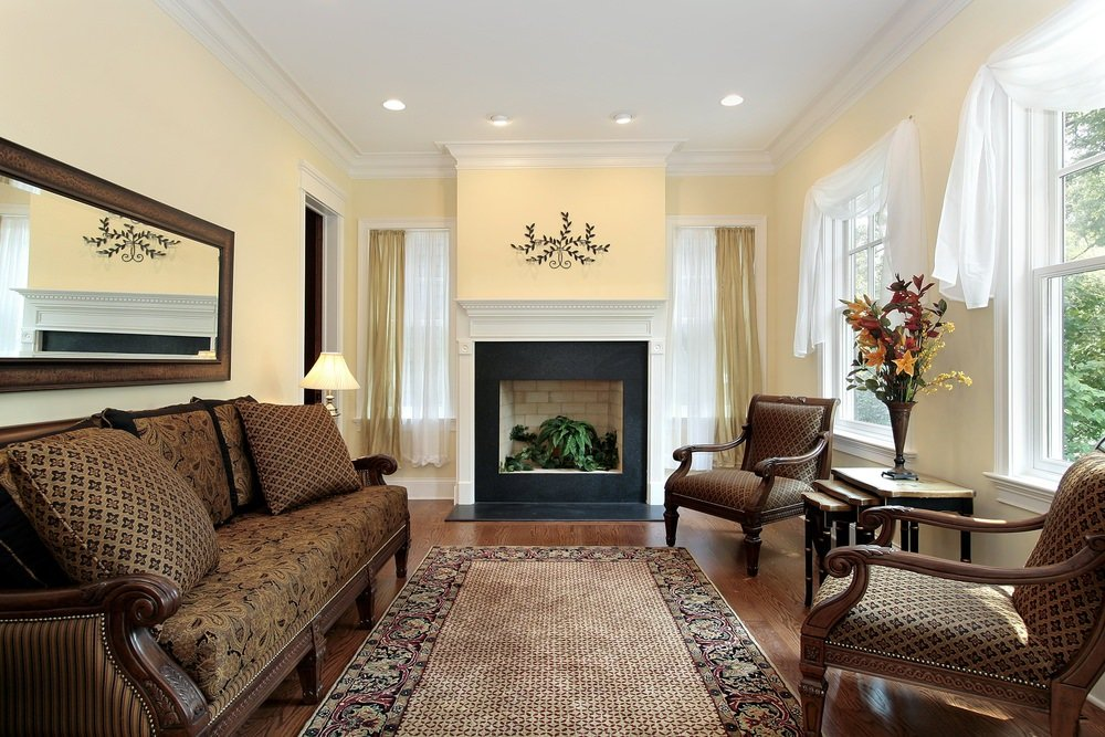 A classy living room featuring an elegant set of seats and a stylish rug covering the hardwood flooring. The beige walls with white window curtains look perfect together.