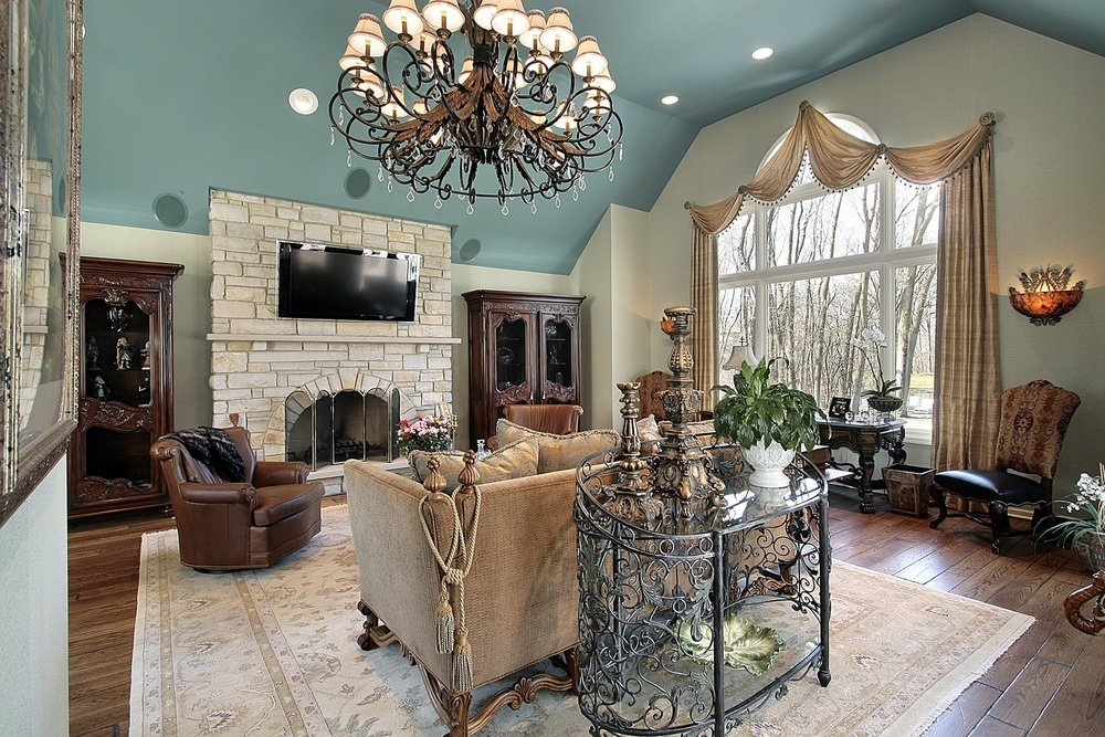 A formal living room with elegant furniture sets and a large area rug, along with a brick fireplace and a widescreen TV on top. The blue walls add style to the room, which is lighted by a glamorous chandelier.