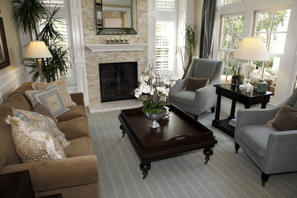 Small living room with stylish carpet flooring matching the gray seats. There's a fireplace as well keeping the room warm.