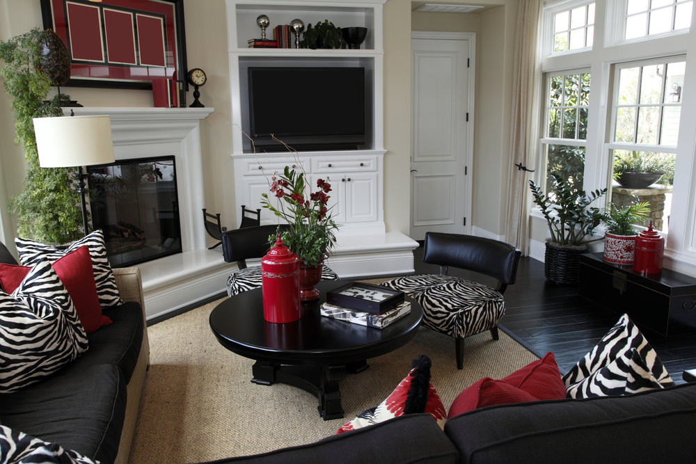 Fabulous living room features black wood plank flooring topped with a brown rug. It has black couches filled with red and zebra pillows that match the chairs.