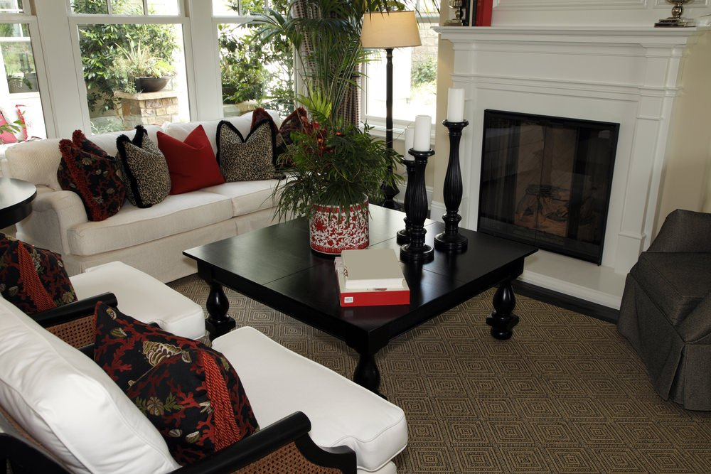 Closeup look of the living room with white sofa and armchairs accented with red and black pillows facing the modular coffee table and fireplace.