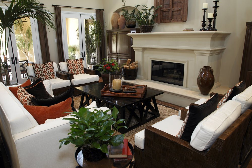 Fresh living room filled with indoor plants and white sofa and chairs. It includes a black coffee table that faces the marble fireplace topped with vintage candle holders.